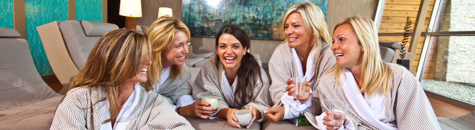 Five young women in spa robes enjoy time together in lounge area as they await their spa treatments at Mt. Hood Oregon Resort