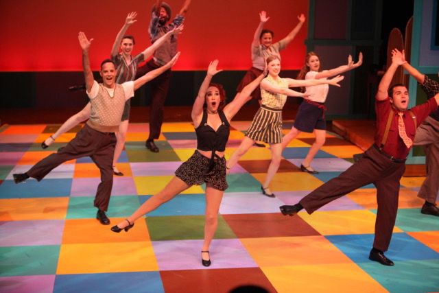 Enthusiastic troupe of theater performers belt out a song while dancing on a stage of multi-color squares