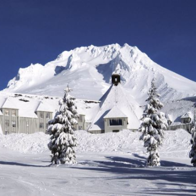 Trees on ski run, historic Timberline Lodge and Mt. Hood all covered in snow on a blue sky day in Oregon's Mt. Hood Territory