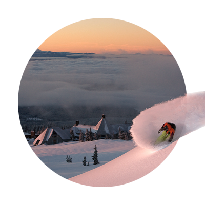 Downhill skier cutting a rooster tail in fresh powder on run above Timberline Lodge with view of cloud covered valley below