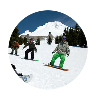 With Timberline Lodge and Mt. Hood behind them, three snowboarders follow in a line during a lesson at Timberline Ski Area.