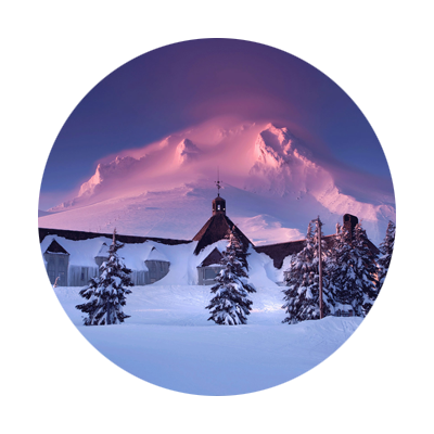 Snow covered trees and historic Timberline Lodge with Mt. Hood's snow appearing pink in the alpenglow of sunset