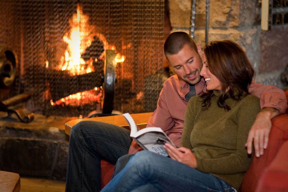 couple reading a book and laughing on the couch in front of a fireplace at Timberline Lodge in Oregons Mount Hood Territory