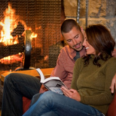 Smiling young couple snugglling with a book on couch in front of Timberline Lodge's massive lobby fireplace with roaring fire