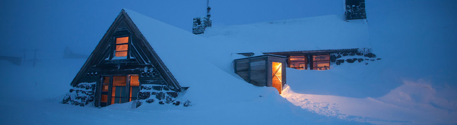 Timberline's Silcox Hut high on Mt. Hood buried in snow halfway up some of its windows seen lit from the interior at night