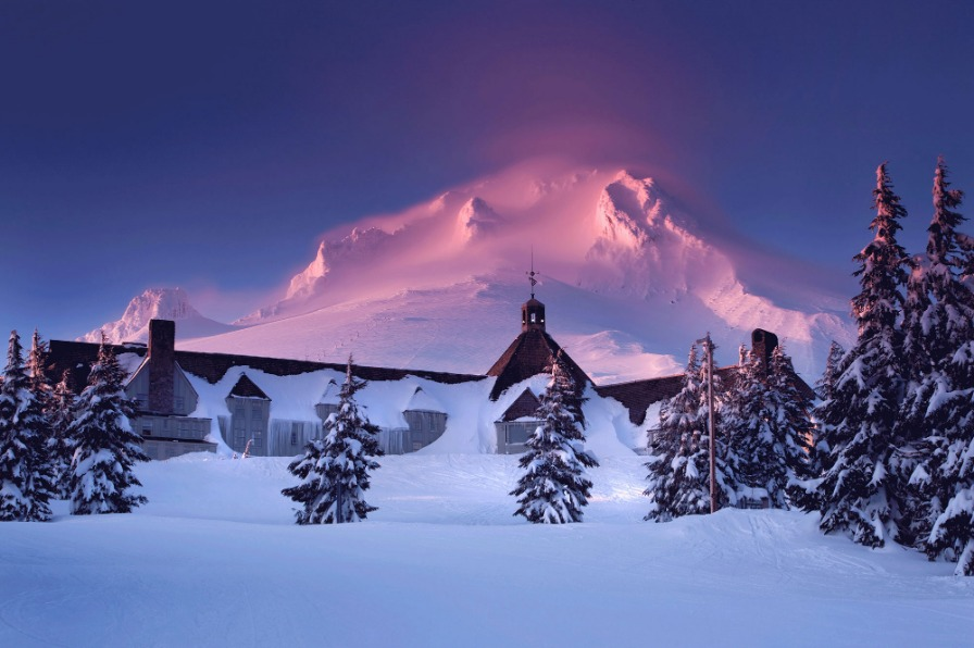 Mt. Hood glows pink behind Timberline Lodge at sunset