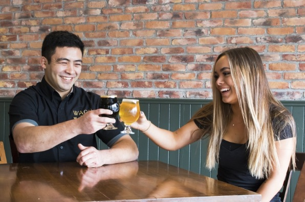 Happy young couple toast their glasses of dark stout and golden cider at Willamette Ale and Cider House in West Linn