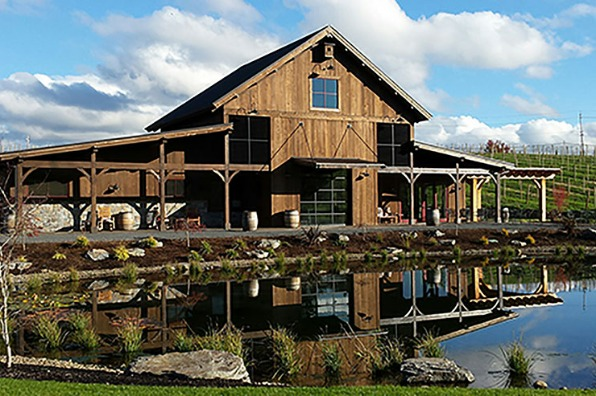 Rustic wooden, open beamed Barrel House tasting room with stocked trout pond sits among rows of grapes at Tumwater Vineyard
