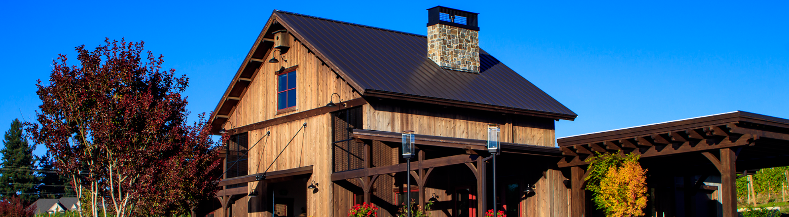 Tumwater Vineyard's rustic barrel house tasting room exterior with covered patio and rock rimmed pond high on Pete's Mountain in West Linn