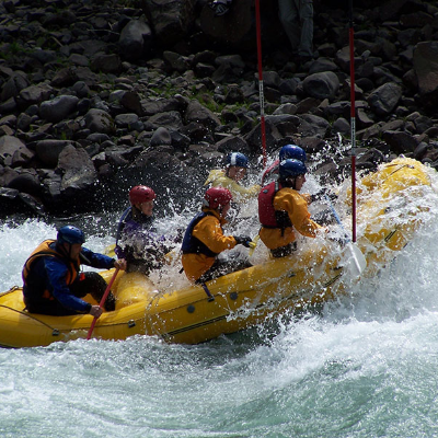 Team of whitewater rafters in large yellow rubber raft encounter large waves in the Upper Clackamas Whitewater Festival competition