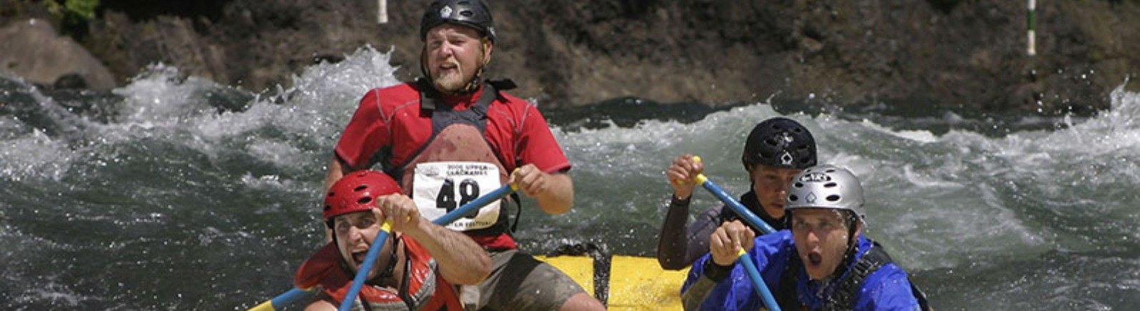 4 male competitors go all out in the rafting competition at the Upper Clackamas Whitewater Festival in Estacada in Oregon's Mt. Hood Territory