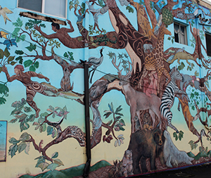Colorful Tree of Life mural with humans and exotic animals painted on side of building in downtown Estacada