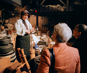 Woman in pioneer period clothing gives a butter churning demo to guests at the End of the Oregon Trail Interpretive Center