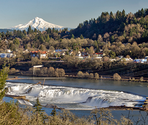 A distant Mt. Hood rises over the Oregon City hillside as frothy whitewater rushes over Willamette Falls on Willamette River