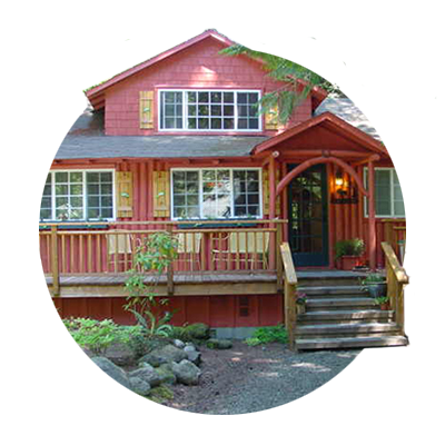 Two-story red log cabin with wraparound porch, one of hundreds of vacation rentals in Oregon's Mt. Hood Territory.