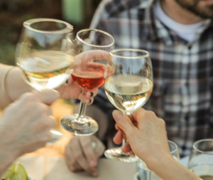 Close-up of hands holding three glasses of wine in a toast during a summer Dinner in the Field