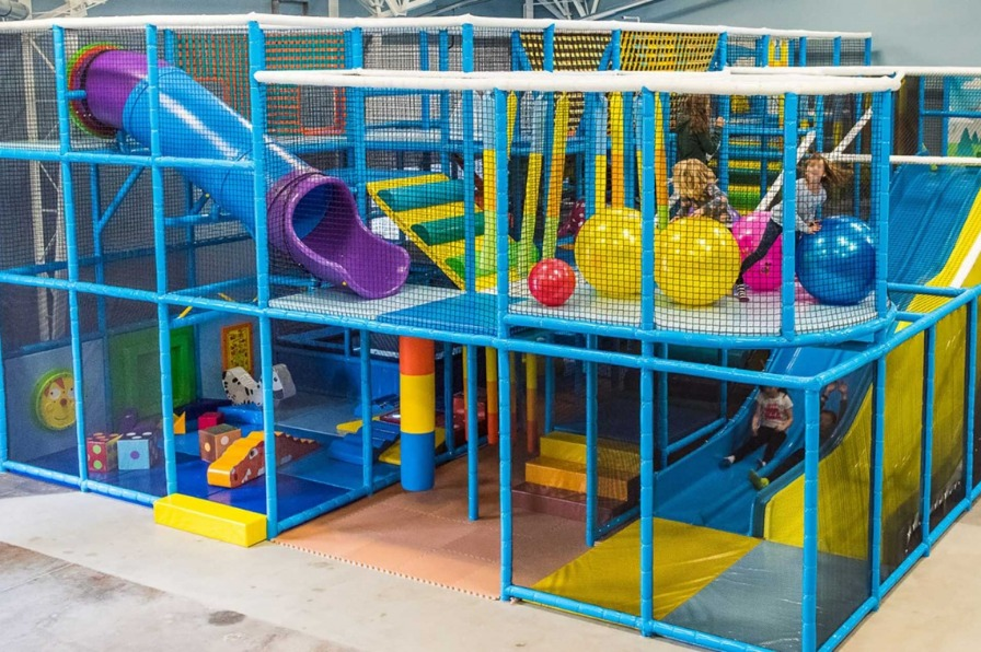 Four kids play on 2 levels of Wippersnappers indoor playground with three slides, oversized dice and toys and colorful balls.