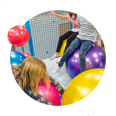 Three children bounce on large yellow, purple and pink exercise balls at Wippersnappers, an indoor kids' play place in Sandy