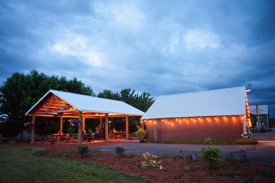 Whiskey Hill Winery tasting room and covered patio lit with strings of lights at night in Oregon's Mt. Hood Territory