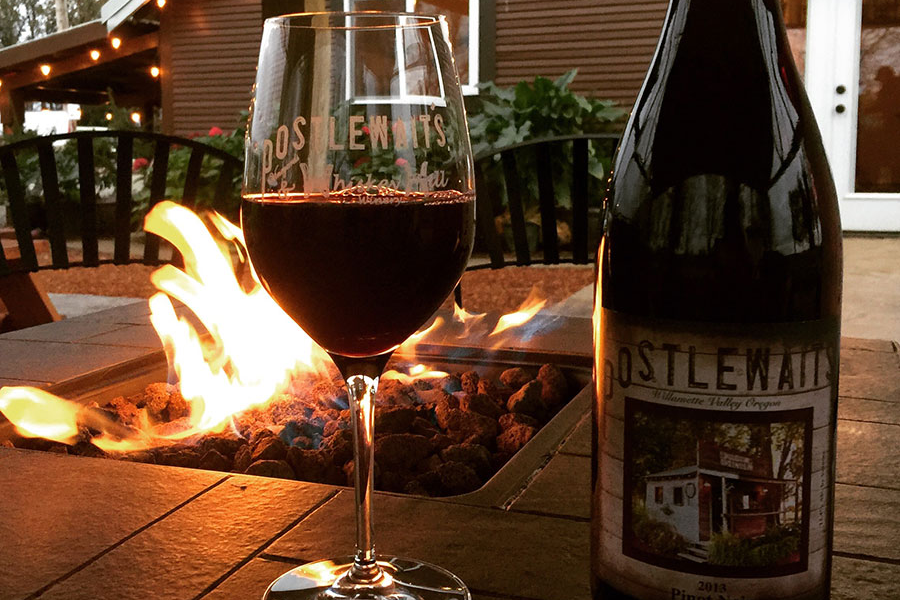 Glass and a bottle of Postlewait red wine sitting on rim of outdoor fire pit at Whiskey Hill Winery tasting room in Canby