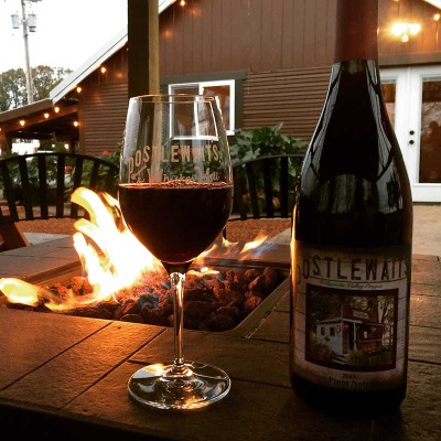 Bottle and glass of Postlewait red wine sit on the tile edge of the flaming fire pit at Whiskey Hill Winery in Canby in Mt Hood Territory