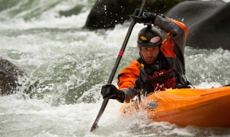 Whitewater kayaker with GoPro camera on helmet paddles his way through boulders and rapids during the Sandy River Showdown.