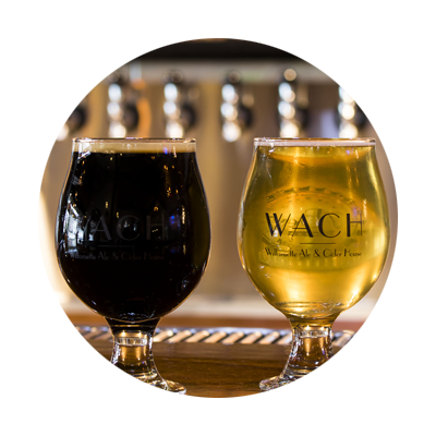 Large glass of dark beer and a glass of golden cider, libations served at Willamette Ale & Cider House