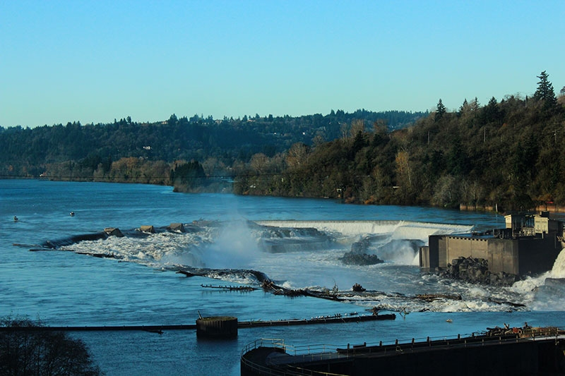 Up close shot of Willamette Falls on the Willamette River with blue all around and white cascading river flowing down the falls in Oregons Mt. Hood Territory.