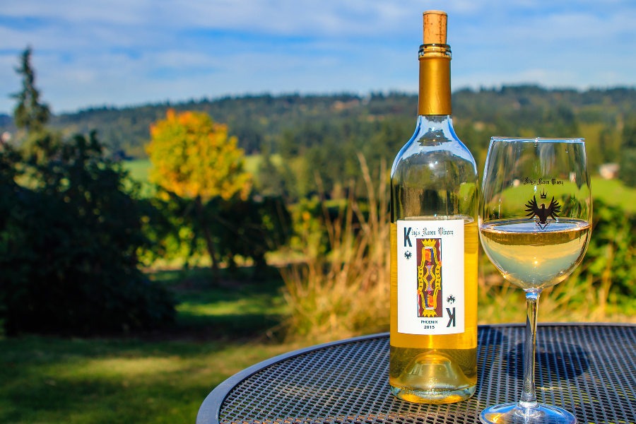 Hillside of fall colored trees popping up among firs is perfect backdrop for the glass and bottle of King's Raven Pinot Gris