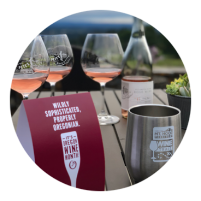 Wine bottle and 3 glasses of rose' and an Oregon Mt. Hood Territory stainless wine glass with Oregon Wine Month table tent.