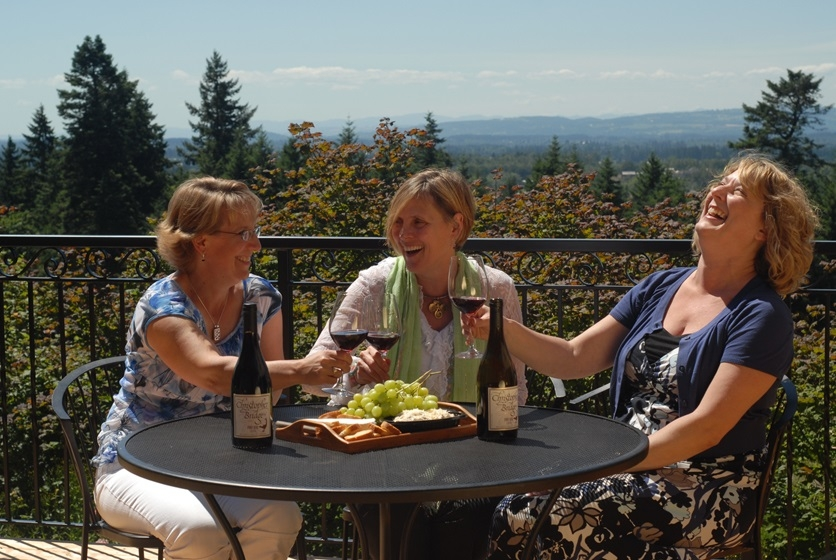 Friends enjoy great conversation and wine on the tasting room patio overlooking the Willamette valley at Christopher Bridge Cellars in Oregons Mt. Hood Territory.