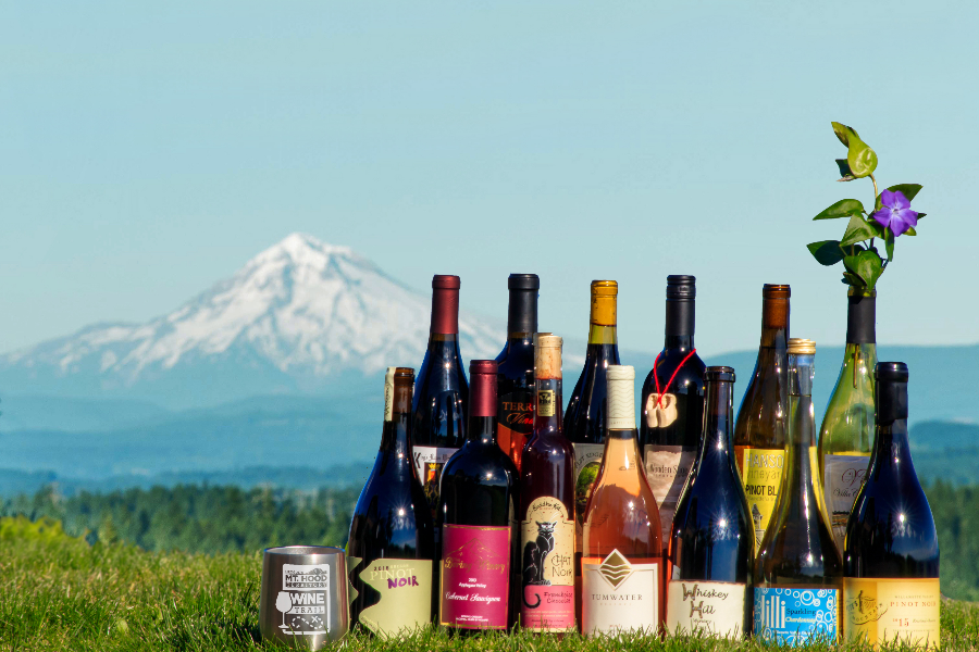 Collection of wine bottles from Mt. Hood Territory wineries staged outdoors on grass with Mt. Hood in background rectangular