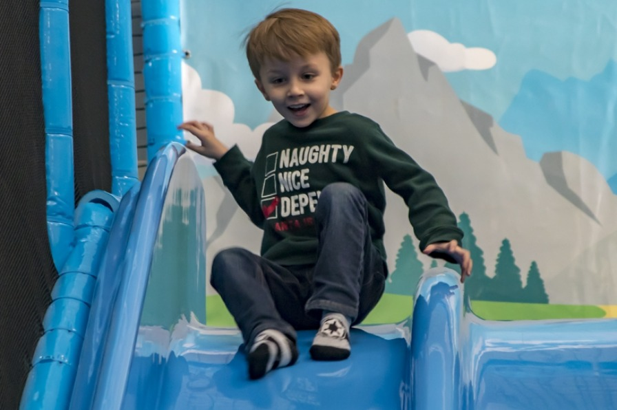Young smiling boy with sock on one foot and shoe on the other is perched at top of a blue indoor slide anticipating his ride