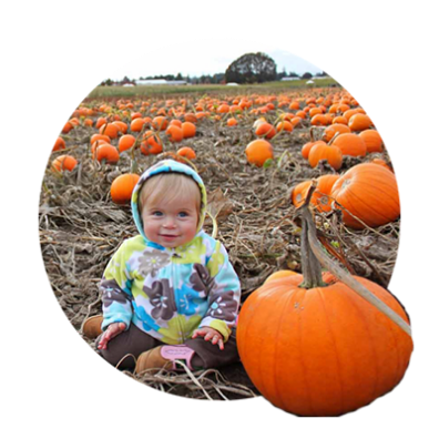 Blonde cherub faced toddler in floral hoodie sits among hundreds of orange pumpkins at Wooden Shoe Farm's pumpkin patch.