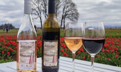 Two bottles of Wooden Shoe wines - one a pink and one a red - and two filled glasses with field of red tulips in background
